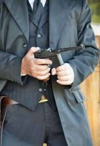 The holster design used was for an original Mauser C96, so the Umarex does not fit with the magazine attached (unless the holster had a cutout for the extended length of the magaizne. Here the author pulls a full magazine from his coat pocket and inserts it into the magazine well.