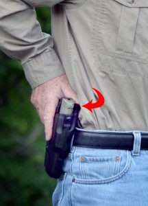 The author demonstrates drawing the CP99 Compact from the Safariland ALS holster. Note the thumb depresses the locking release (arrow) as the pistol is drawn. Also note the position of the trigger finger on the outside of the holster.