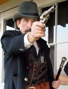 Bat Masterson (portrayed here by the author from Guns of the Old West) wore his Colt cross draw style, butt forward and covered, making it almost impossible for anyone to disarm him from behind. It has also been written that he carried two guns, and in some instances he did when heading up a posse or on the open plains, but in town where most everything happened at close range, it was the shorter barreled Colt carried cross draw that Bat preferred over any other.