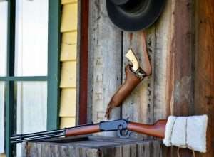 "With a sheepskin tied around the stock to disguise the black plastic buttplate and the hood removed from the front sight, the Walther looks very much like an 1894 Winchester. (Shown with a custom holster by Chisholm's Trail Leather, an Umarex Colt SAA, and ""Bohannon"" hat courtesy of Golden Gate Western Wear)"
