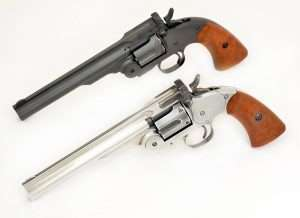 The original Bear River gun, top, and the refinished antiqued model are shown together. Note that the faux case colors on the latch go around the top of the barrel as it is a separate piece. The channel down the center of the barrel is also left darker as are the sides of the front sight. The polished top of the front sight easily picks up in the blued V notch of the stud latch. The polished cylinder still remains a couple of shades darker, especially inside the cylinder flutes.