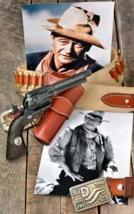 "Among the various John Wayne commemorative models, this version has the weathered finish like so many of the Colt Single Actions used in his films. The guns come with John Wayne ""Duke"" medallions inlaid into each grip panel. While those grips are actually plastic they look more like wood than a lot of wood grips! (Holster by John Bianchi Frontier Gunleather, Red River D belt buckle by Chisholm's Trail Leather)"