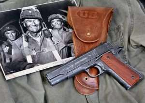 The new John Wayne Model 1911A1 is the first John Wayne semi-auto in the series of John Wayne commemorative airguns. (Shown with a publicity photo of Wayne in The Longest Day, and a copy of a WWII era JT&L Model 1942 holster from World War Supply).