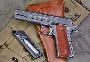 The John Wayne signature and name on the left side of the slide and 1911 Commemorative distinguish this model from the previous limited edition WWII commemorative 1911A1 model. (Holster and web magazine belt courtesy World War Supply)